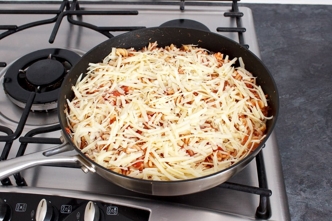Tuna pasta bake topped with grated cheese in a large frying pan on a hob