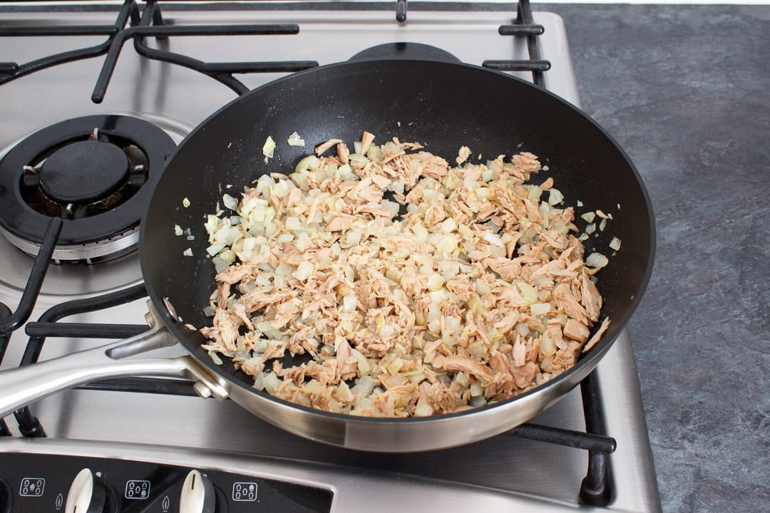 Tuna, onion and garlic cooking in a large frying pan on a hob