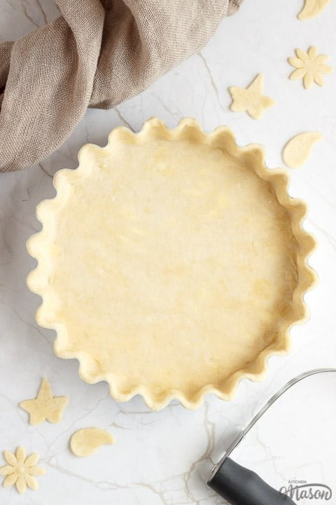 A loose bottomed fluted tart tin lined with unbaked shortcrust pastry surrounded by pastry leaves, a pastry blender and some fabric.