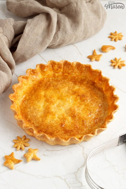 A golden baked shortcrust pastry case surrounded by golden pastry leaves, a pastry blender and a piece of fabric.