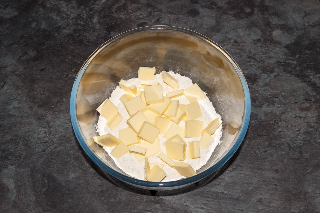 Flour and salt in a large glass bowl with cubed cold butter on top