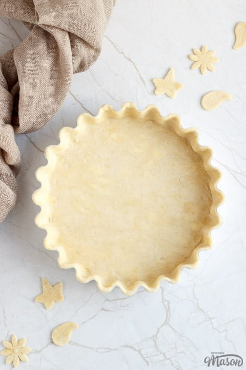 A loose bottomed fluted tart tin lined with unbaked shortcrust pastry surrounded by pastry leaves and some fabric.