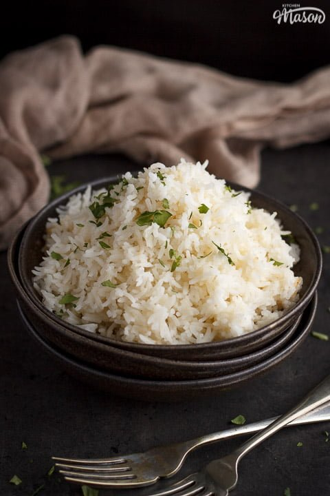 freshly cooked rice scattered with chopped coriander in the top bowl of a stack of 3 with a fork next to it