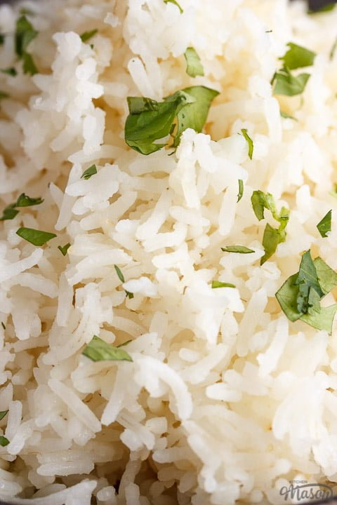 freshly cooked rice scattered with chopped coriander in the top bowl of a stack of 3