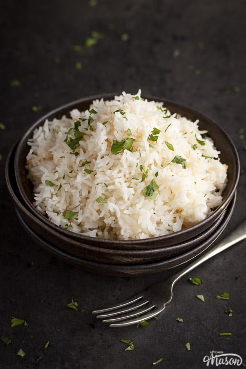 freshly cooked rice in the top dish of a stack of 3 with a fork next to it