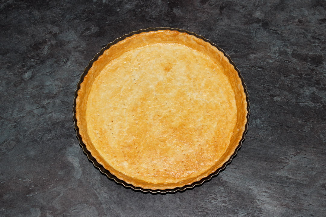 Blind baked shortcrust pastry case in a round fluted tart tin on a work surface