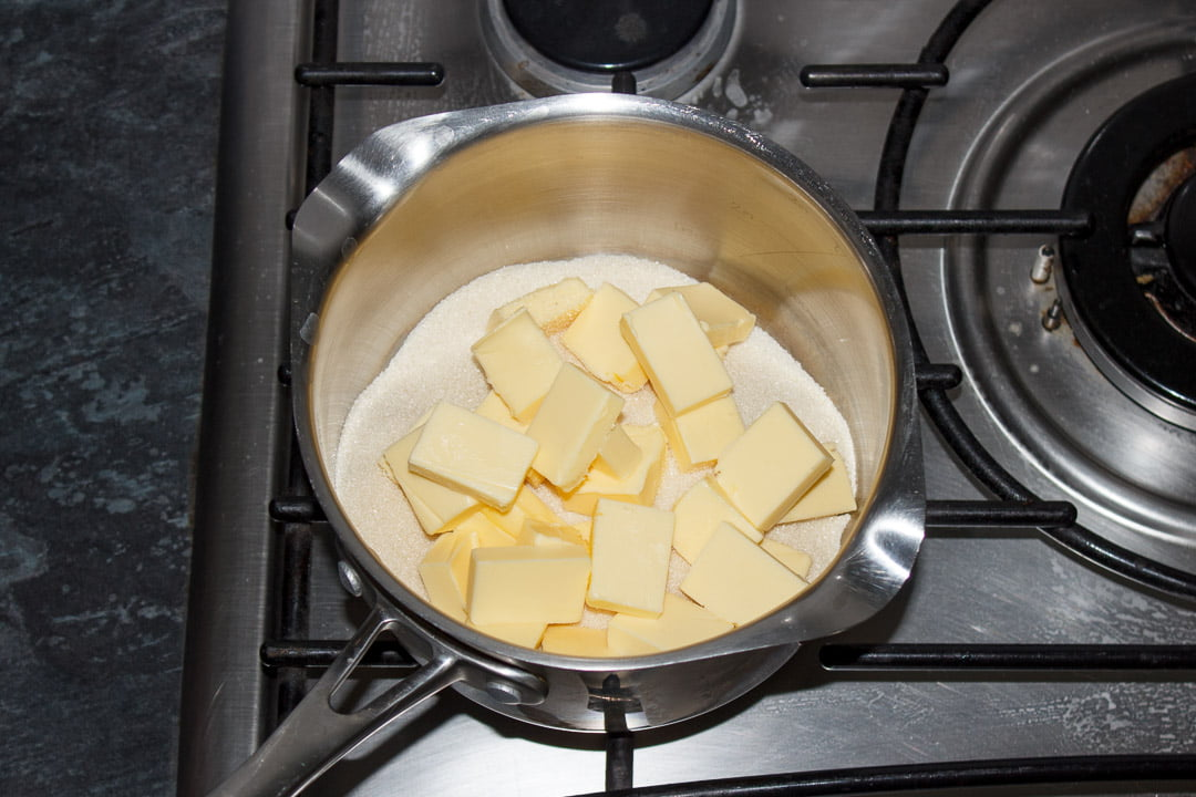 Cubed butter and sugar in a large saucepan set on a stove top