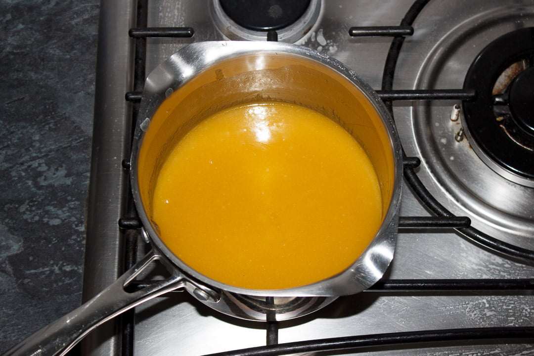 Melted butterscotch tart filling in a large saucepan on a stove top