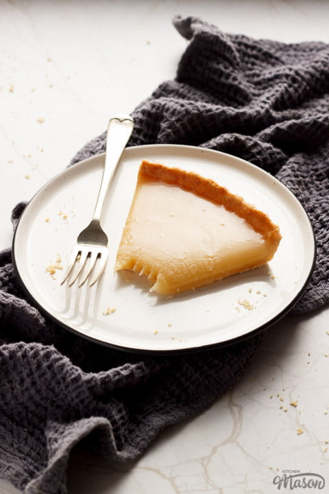 A slice of butterscotch tart on a plate with a fork, on a grey tea towel and white marble work top