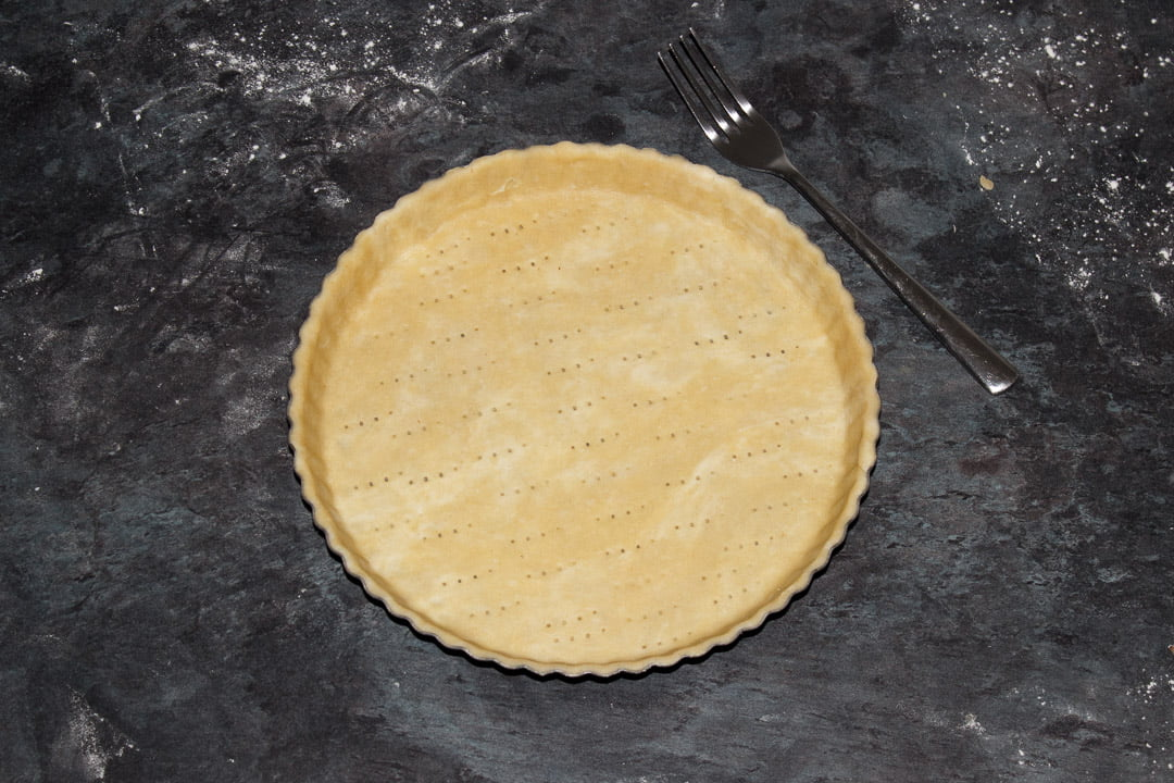 A round fluted tart tin lined with shortcrust pastry and pricked all over with a fork
