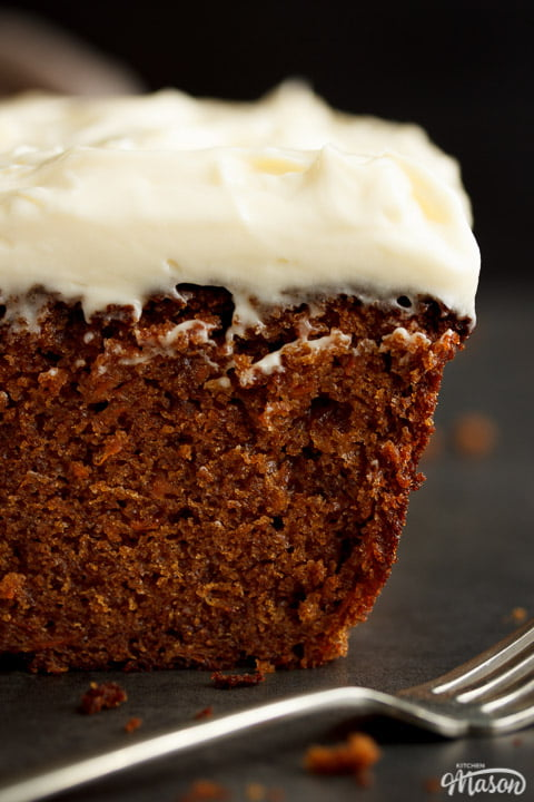 Carrot loaf cake topped with cream cheese frosting on a worktop with a cloth and a fork in the background