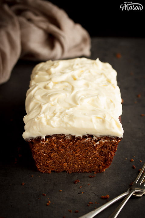 Carrot loaf cake topped with cream cheese frosting on a worktop with a cloth and forks in the background