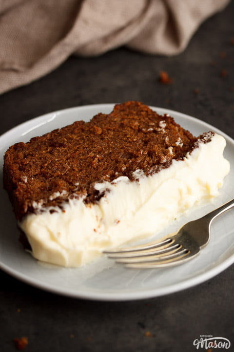 Slice of carrot loaf cake on a white plate with a fork and a cloth in the background