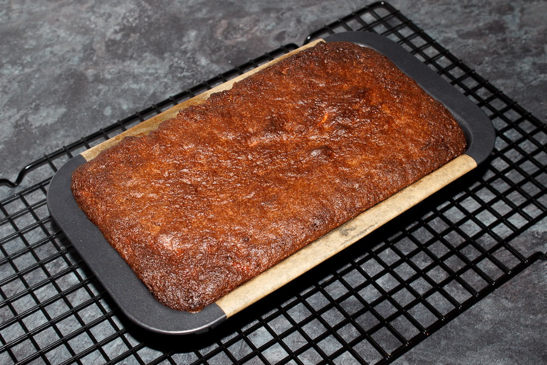 Baked carrot loaf cake in a loaf tin on a cooling rack