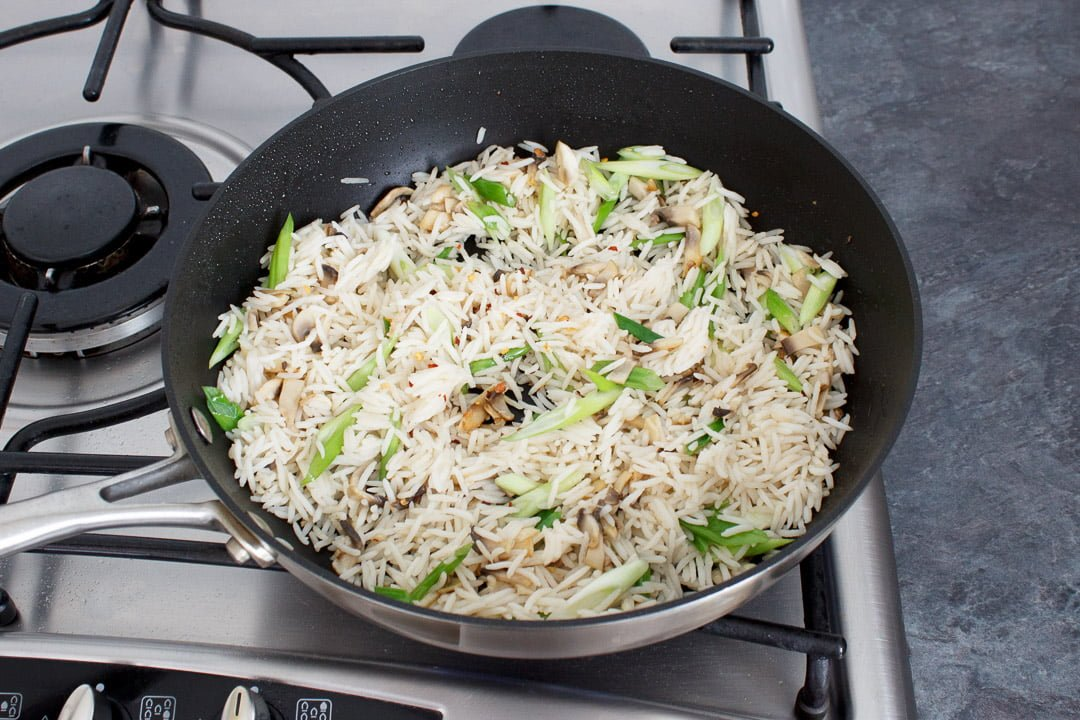 Chopped mushrooms, spring onion and cooked rice frying in a large frying pan on a hob