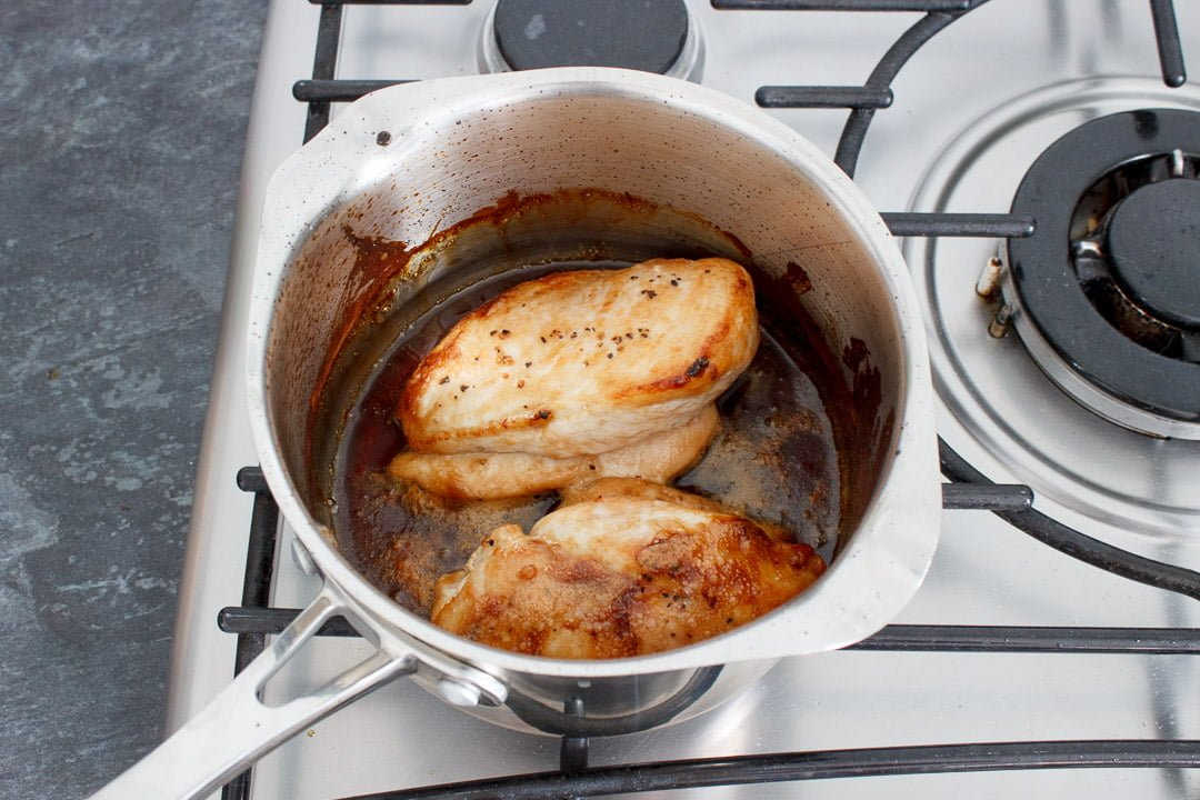 Soy sauce, mirin and caster sugar simmering in a small saucepan with 2 cooked chicken breasts