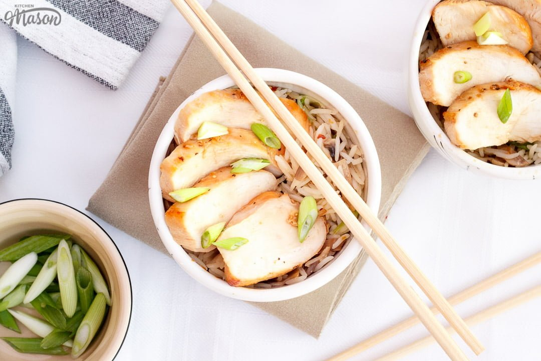 Chicken teriyaki in a small bowl with chop sticks balanced on top