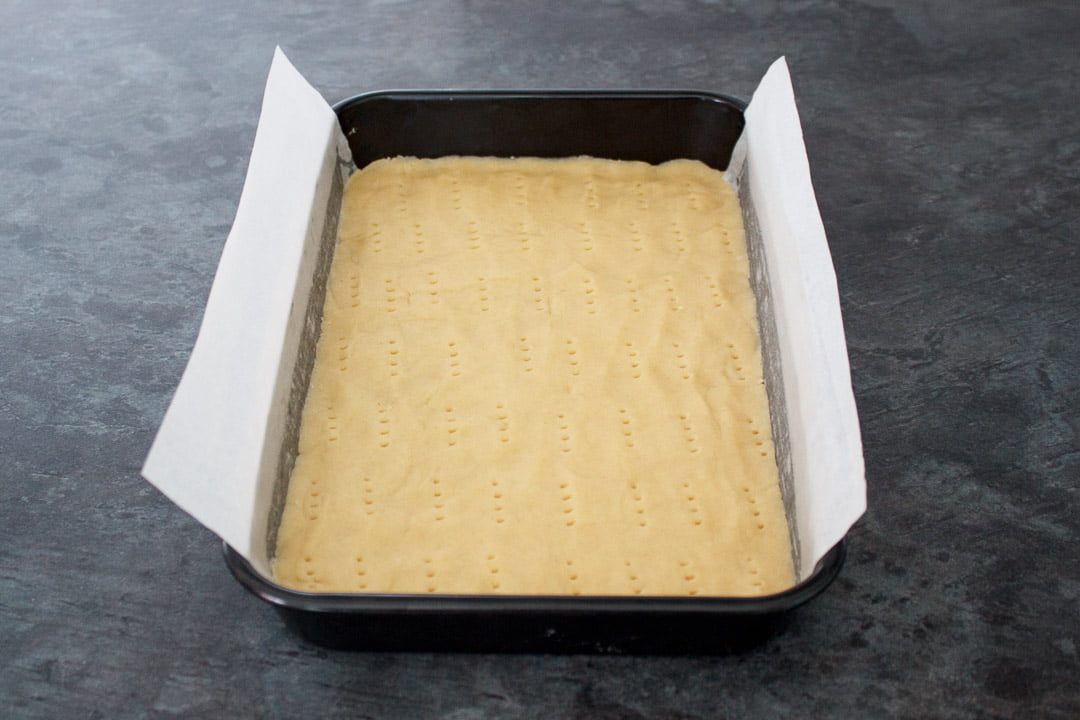 Shortbread dough pressed into the base of a lined rectangular baking tin