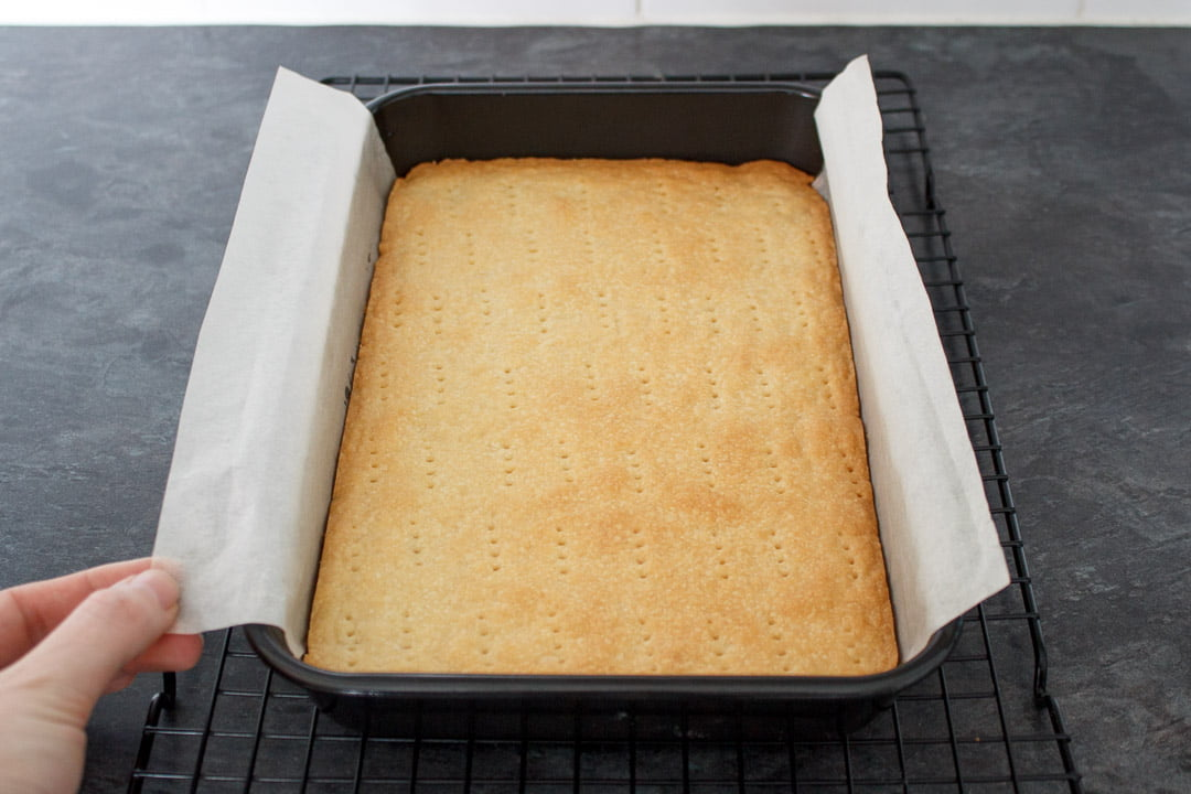 Baked shortbread base in a lined rectangular baking tin