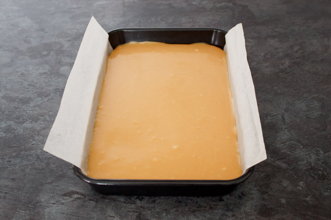 Caramel smoothed over the shortbread biscuit base in a lined rectangular baking tin.