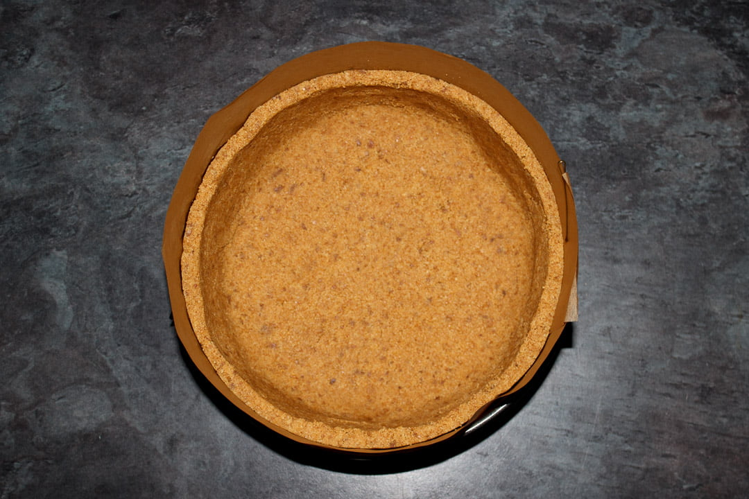 A lined springform pan filled with a digestive biscuit crum pressed into the base and sides