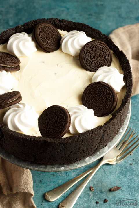 A whole no bake Oreo cheesecake on a cake stand with two forks, a light brown napkin and Oreo crumbs in the background