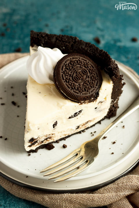 Slice of no bake Oreo cheesecake on a plate with a fork with a light brown napkin and Oreo crumbs in the background