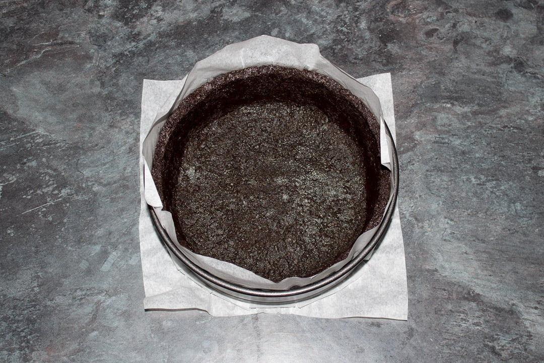 A lined springform pan with buttery Oreo crumbs pressed into the base and sides