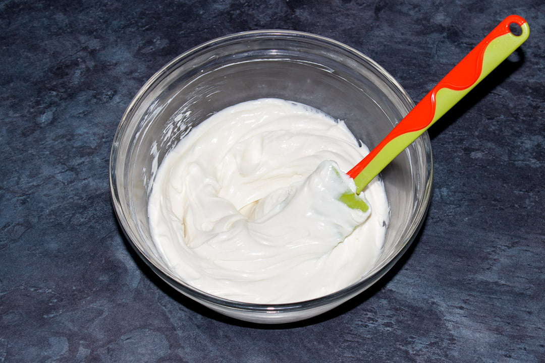 Softened cream cheese, caster sugar and vanilla extract beaten together in a glass bowl with a rubber spatula