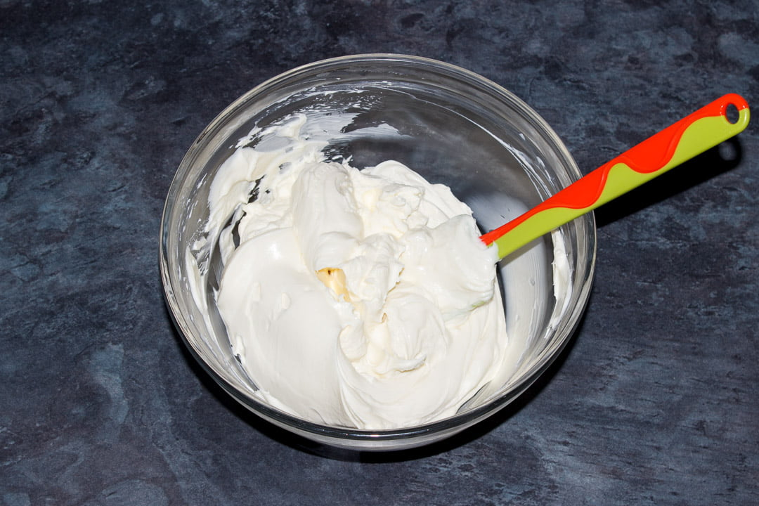 Whipped sweetened cream being folded into a cream cheese mixture with a rubber spatula in a glass bowl