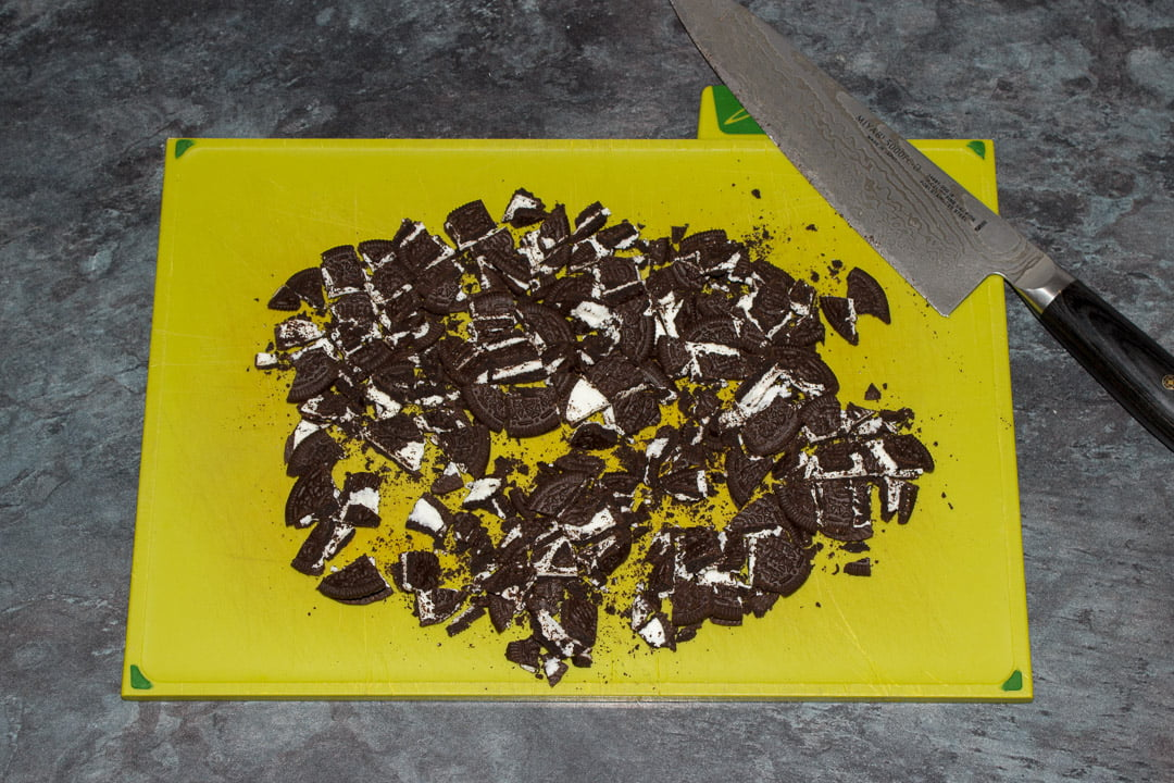 Oreos roughly chopped on a green chopping board with a sharp knife