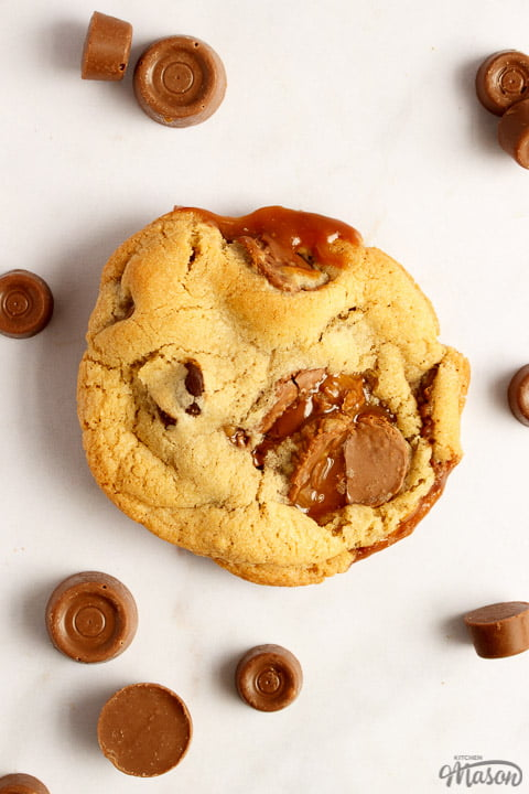 A Rolo cookie on a white marble worktop with large and small Rolos scattered around it
