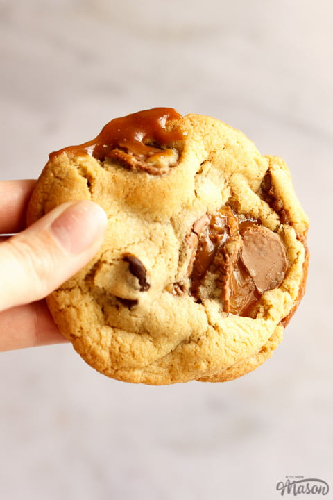 A Rolo cookie being held up in front of a white/grey background