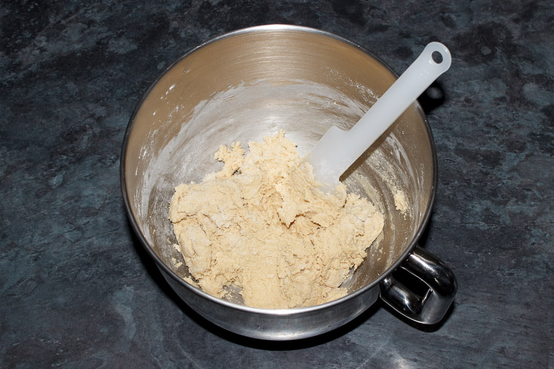 Cookie dough in the bowl of an electric stand mixer with a spatula