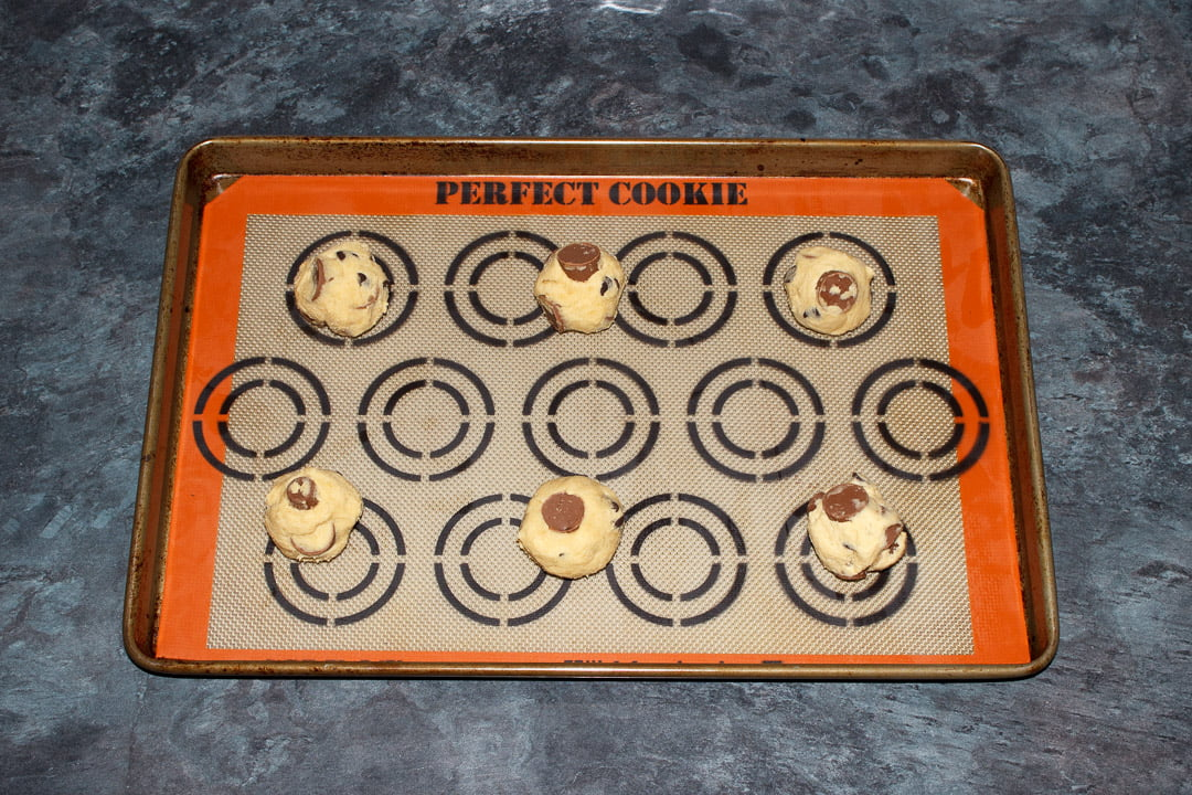 6 Rolo cookie dough balls spaced out on a large lined baking tray