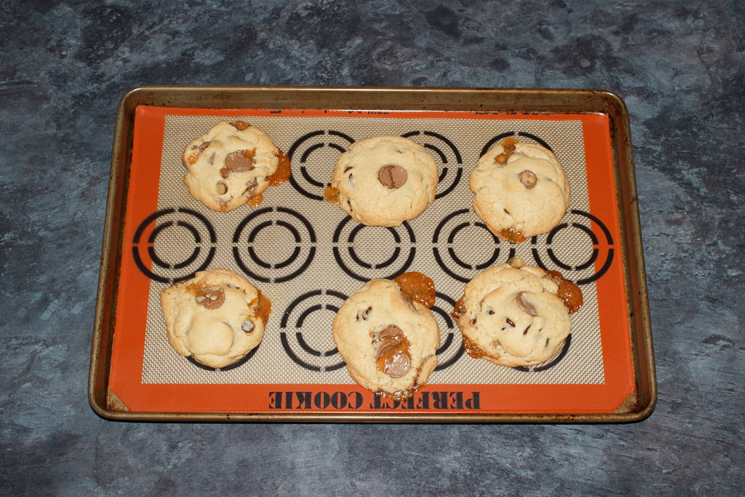 6 baked Rolo cookies spaced out on a large lined baking tray with caramel oozing out