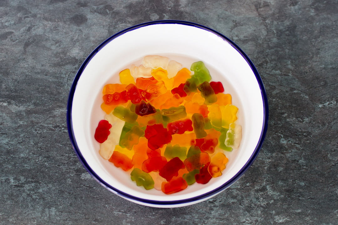 Gummy bears soaking in vodka in a white bowl