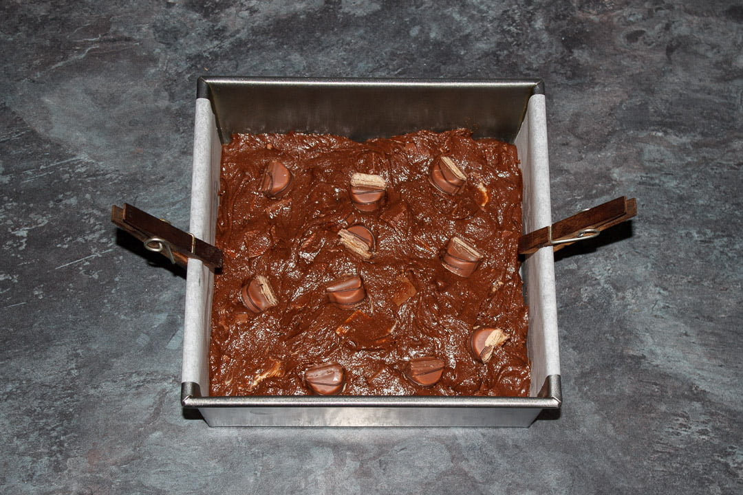 Kinder Bueno Brownie batter in a lined square baking tin with Kinder Bueno Bar pieces pushed into the top