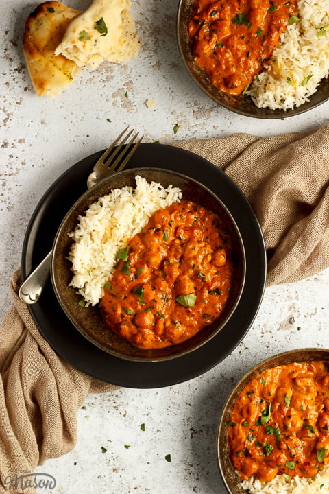 3 bowls of chana masala curry and rice on a textured white background with forks and a light brown napkin