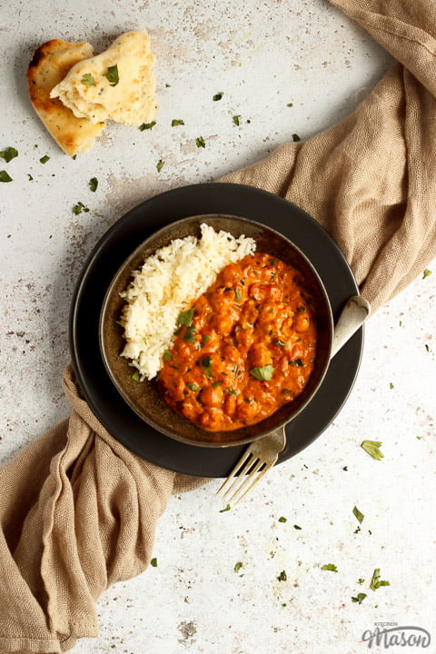 A bowl of chana masala curry and rice with a fork on a light brown napkin with torn naan bread at the side