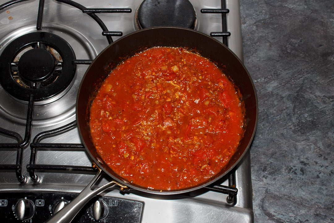 Chana masala curry base in a large saucepan with tinned tomatoes cooking on the stove