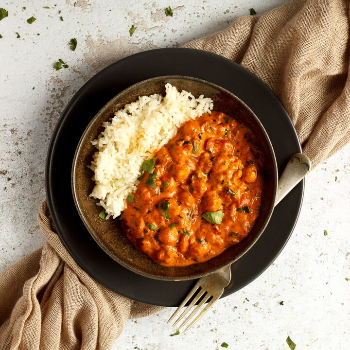 A bowl of chana masala curry and rice with a fork on a light brown napkin
