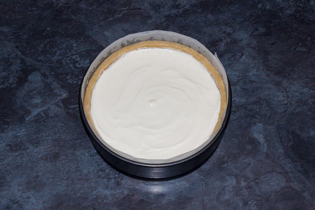 A no bake vanilla cheesecake in a lined springform pan ready for setting in the fridge