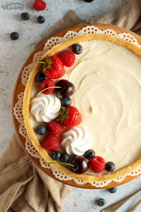 No bake vanilla cheesecake on a cake stand topped with mixed berries, surrounded by a light brown napkin and two forks