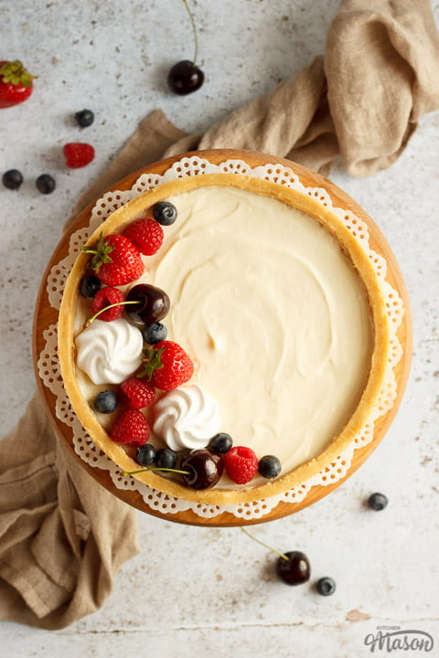 A no bake vanilla cheesecake on a cake stand topped with mixed berries surrounded by a light brown napkin