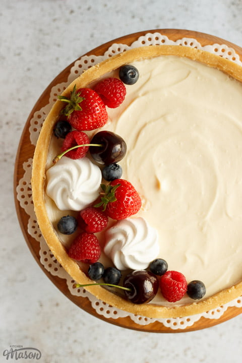 A no bake vanilla cheesecake on a cake stand topped with mixed berries