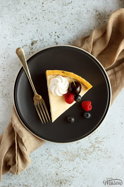 A slice of no bake vanilla cheesecake on a grey plate with a fork, topped with mixed berries, surrounded by a light brown napkin