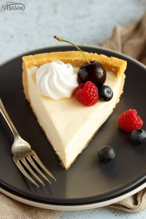 A slice of no bake vanilla cheesecake on a grey plate with a fork, topped with mixed berries