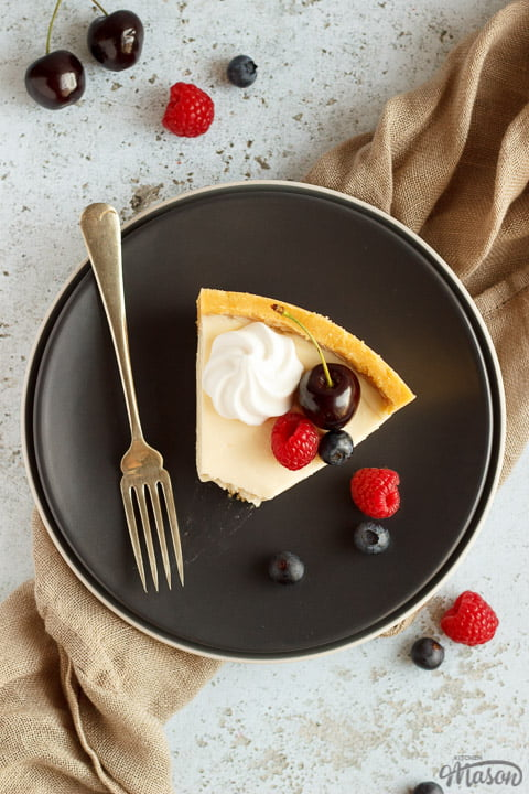 A slice of no bake vanilla cheesecake with a bite taken out of it on a grey plate with a fork, topped with mixed berries, surrounded by a light brown napkin