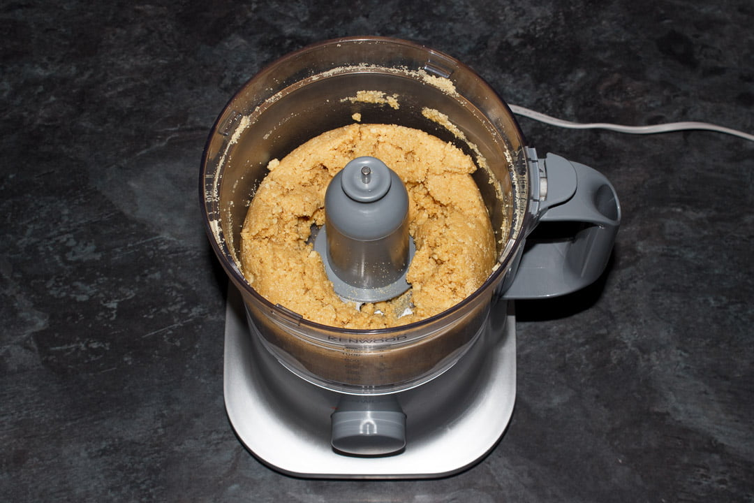 Crushed biscuit crumbs mixed with melted butter in a food processor